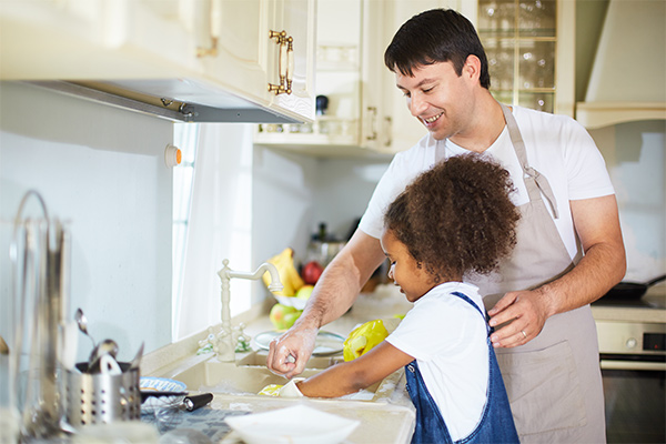 Foster dad doing dishes with young girl
